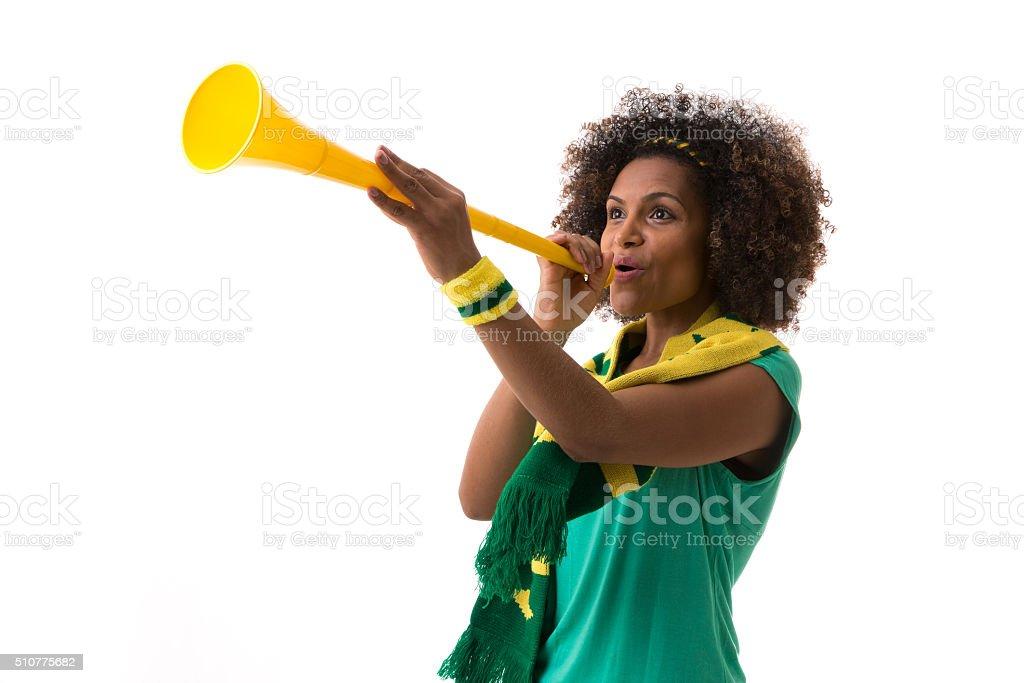 Brazilian woman blowing by vuvuzela on white background stock photo