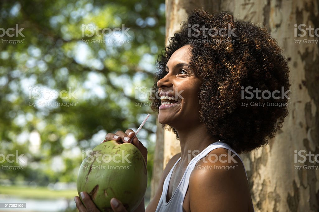 Brazilian woman drinking coconut water in the park stock photo