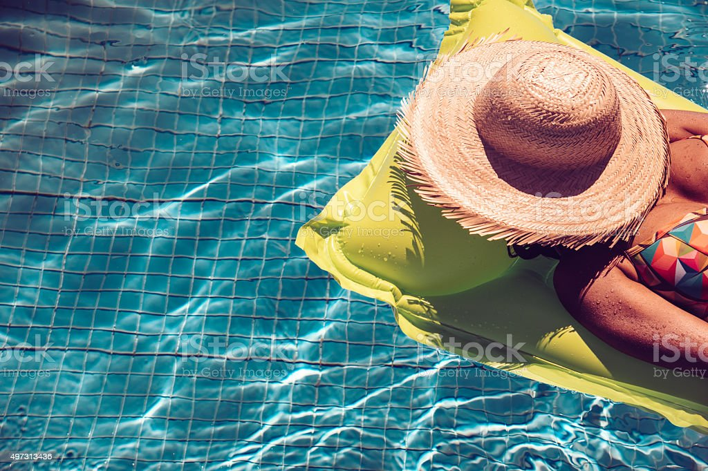 brazilian woman  relaxing on yellow airbed in blue swimming pool stock photo