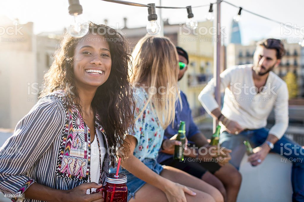 Brazilian woman with friends at rooftop party stock photo