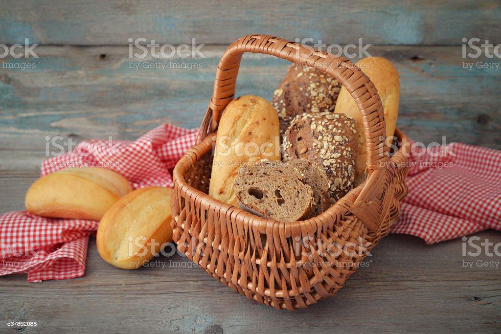 Bread and rolls in wicker basket stock photo
