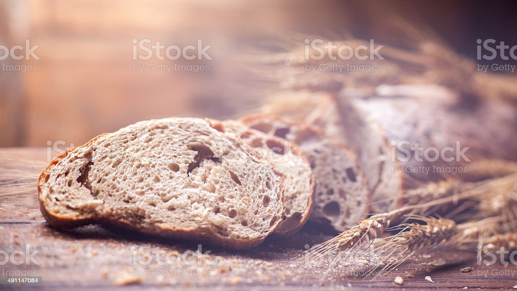 Bread and wheat on wooden table, shallow DOF stock photo