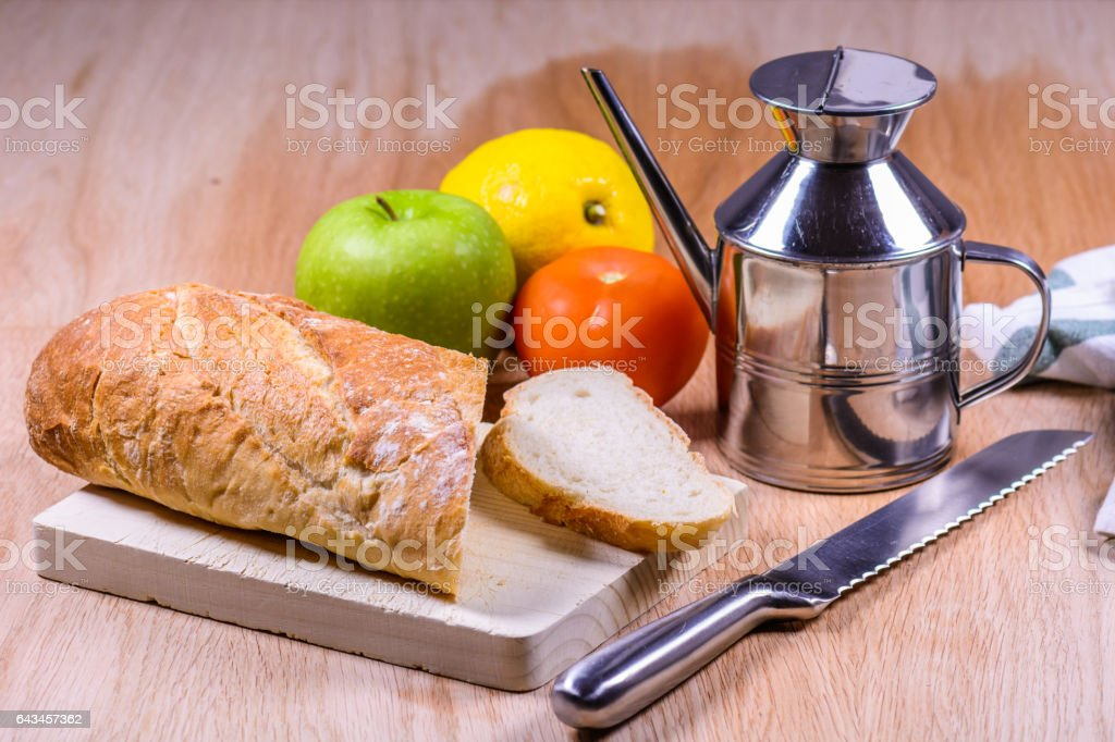 bread artisan on table wood with oilcan, fruits and vegetables stock photo