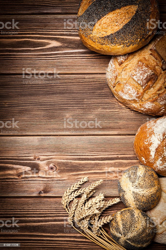 Bread assortment on wooden surface stock photo