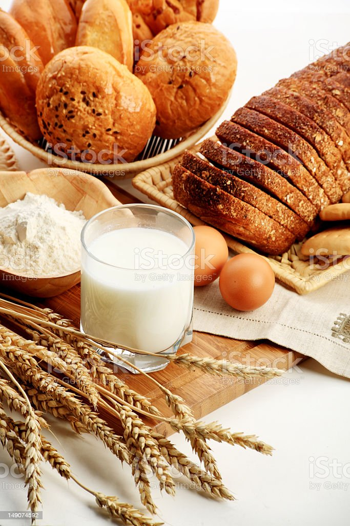 Bread basket and sliced bread next to a glass of white milk stock photo