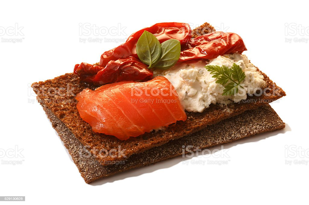 Bread crisp with salmon, soft cheese, dried tomatoes and chervil stock photo