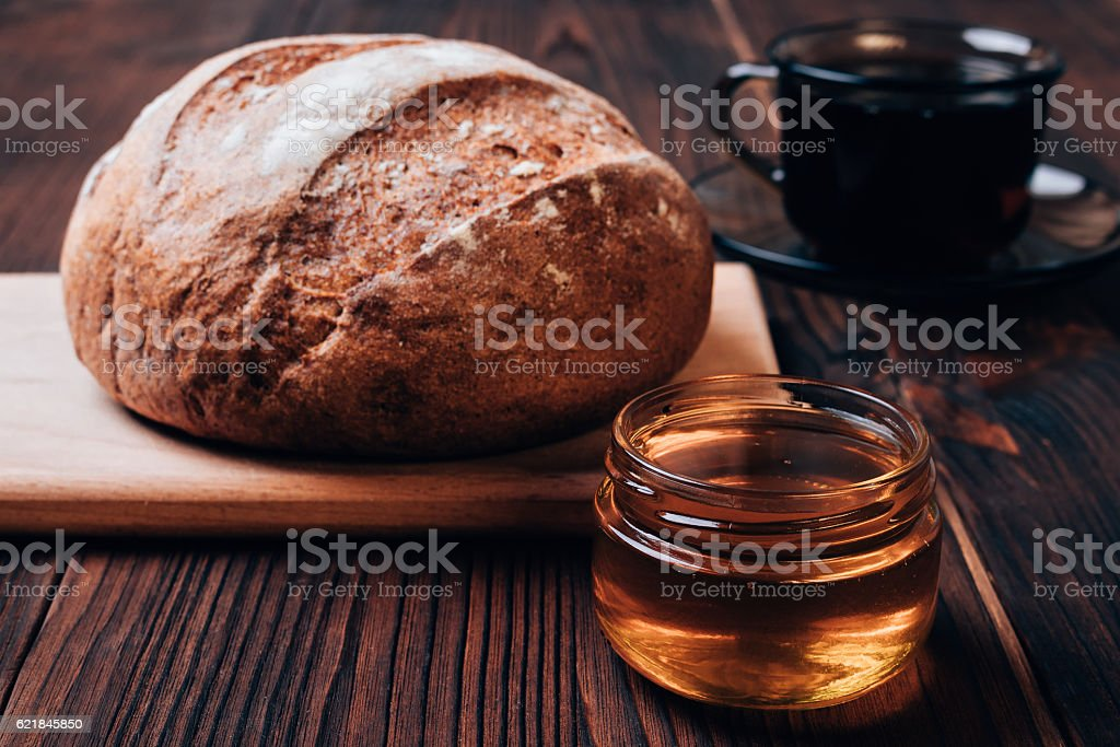 Bread, cup of tea and honey on a brown table stock photo