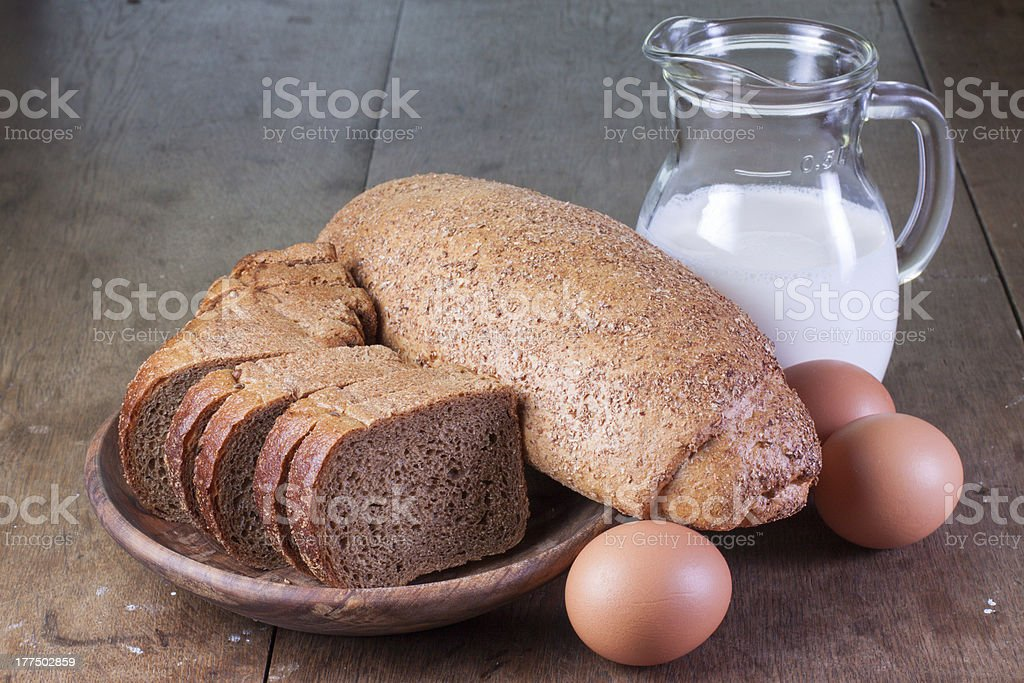 Bread, eggs and milk on old oak wooden table royalty-free stock photo