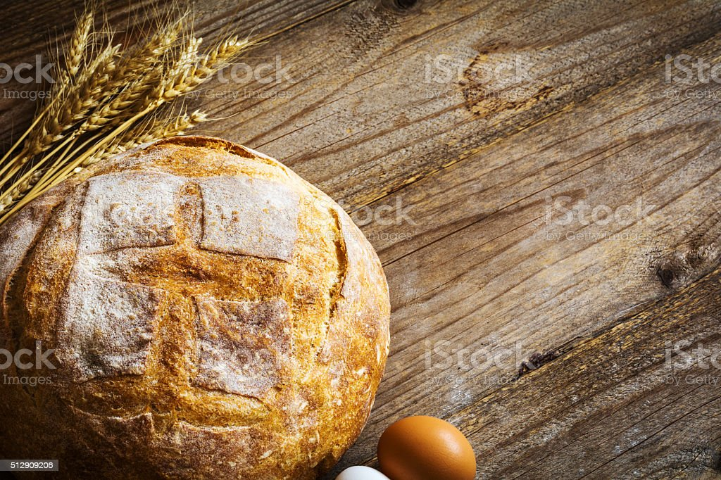 Bread, eggs and wheat ears on wooden table stock photo