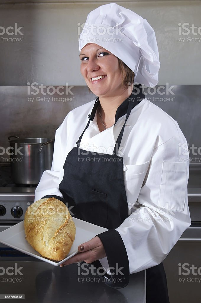 Bread Loaf Presented by Happy Woman Chef in Commercial Kitchen stock photo