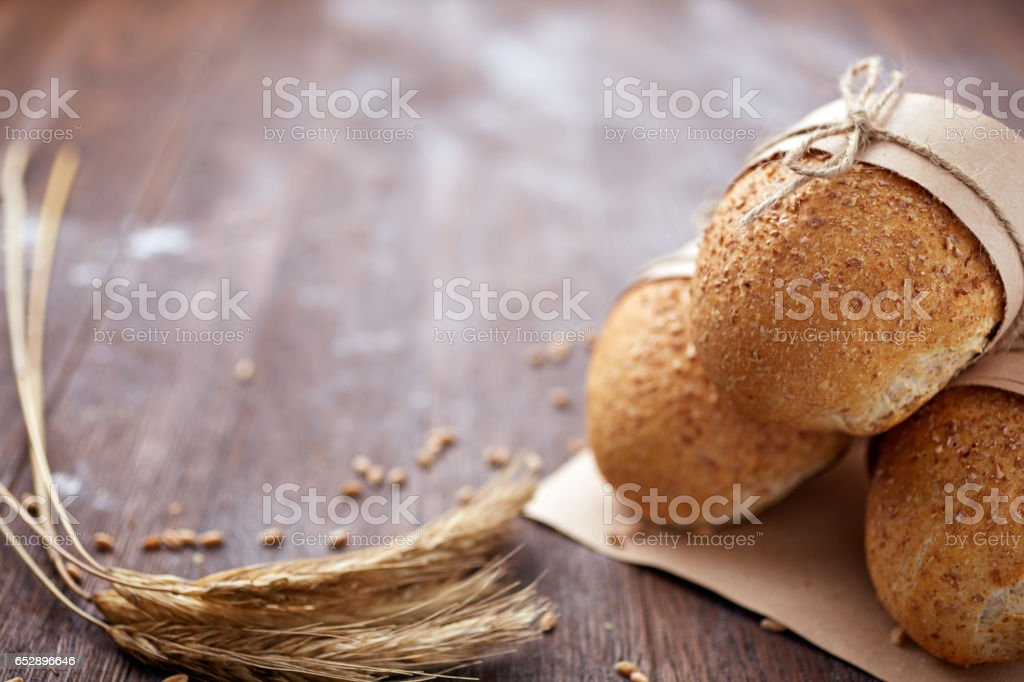 Bread loaf rustic selection of rye, soda, bloomer breads, with granary and oated rolls and ears of wheat. stock photo
