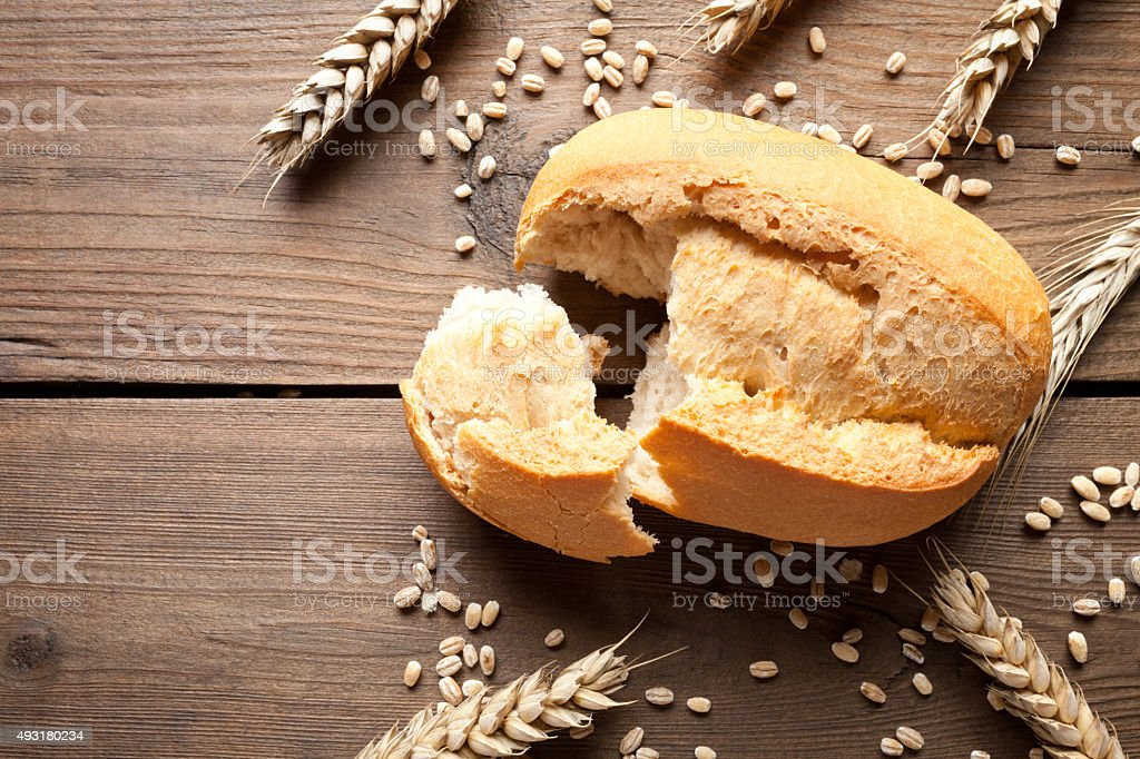 Bread roll and wheat ears on wooden table stock photo