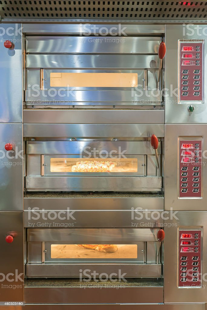 Bread rolls baking in oven at a commercial kitchen stock photo