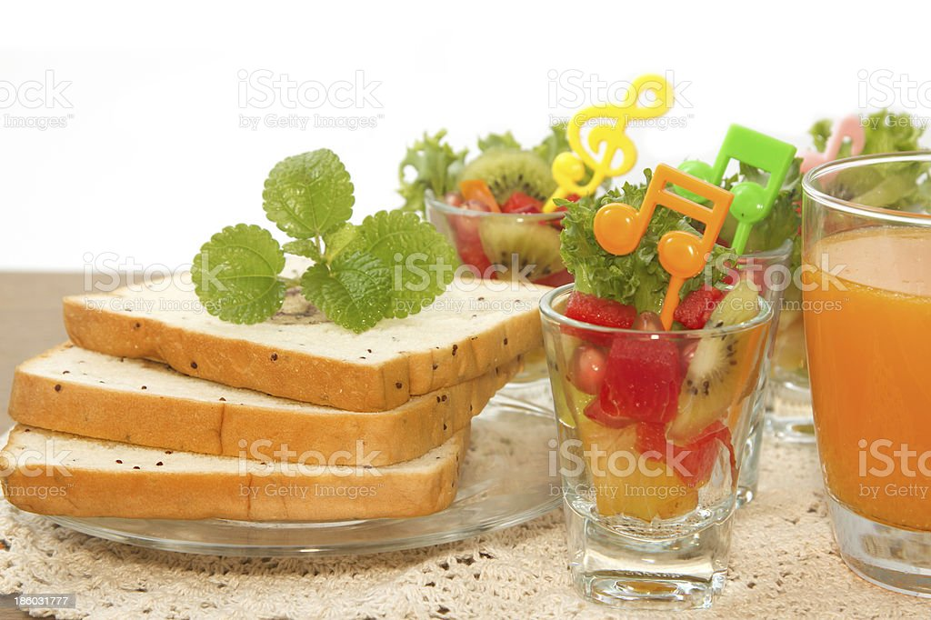 bread slice and fruit salad with orange juice, fusion food royalty-free stock photo
