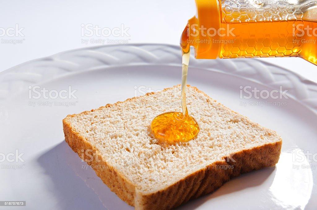 Bread slice with honey stock photo