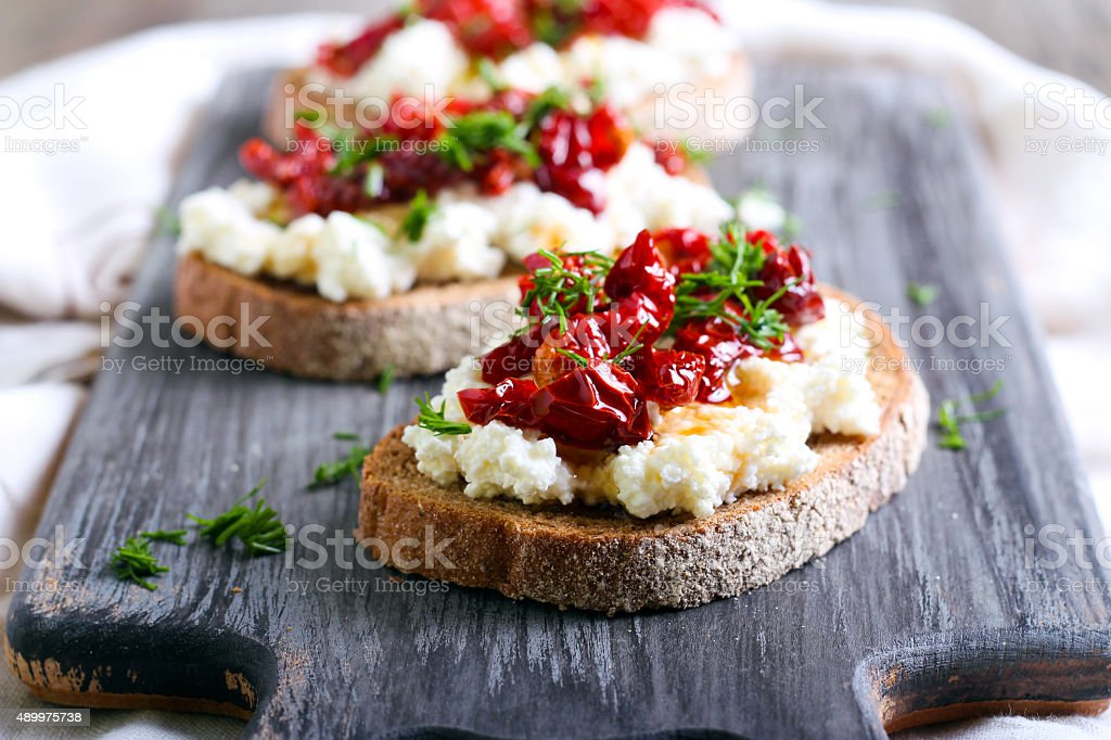 Bread slices with ricotta cheese and, sun dried tomatoes stock photo