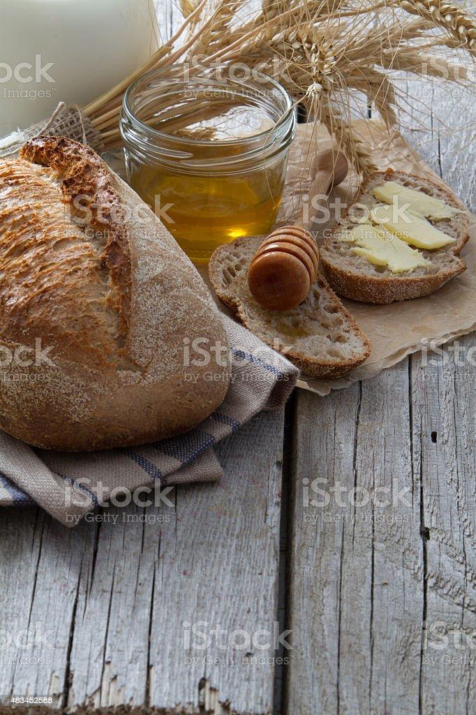 Bread, wheat, rye, honey, milk on rustic wood background stock photo