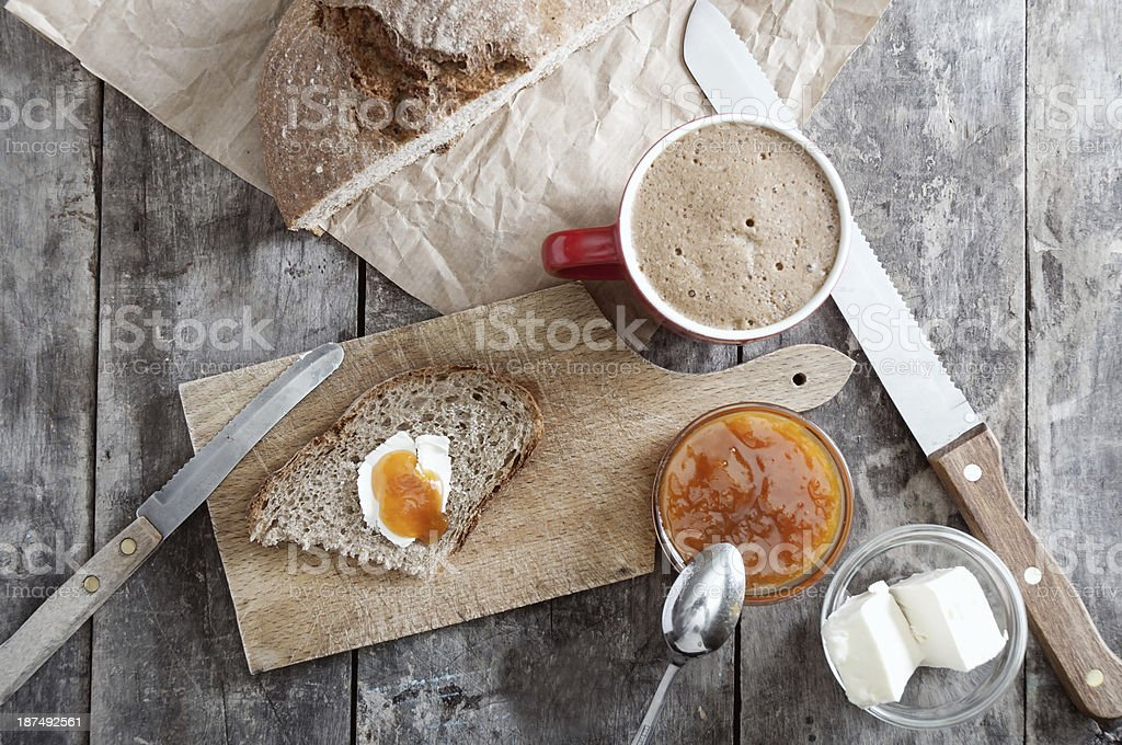 Bread with butter and jam on a wooden cutting board stock photo