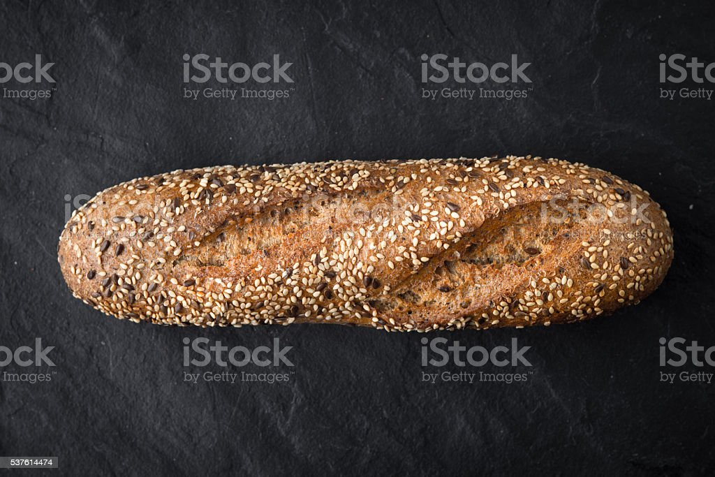 Bread with grains and seeds on  stone table top view stock photo
