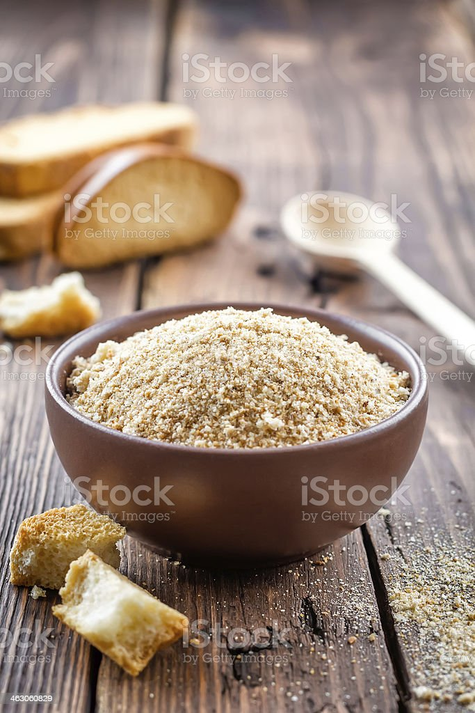 Breadcrumbs in a brown bowl on a wooden table stock photo