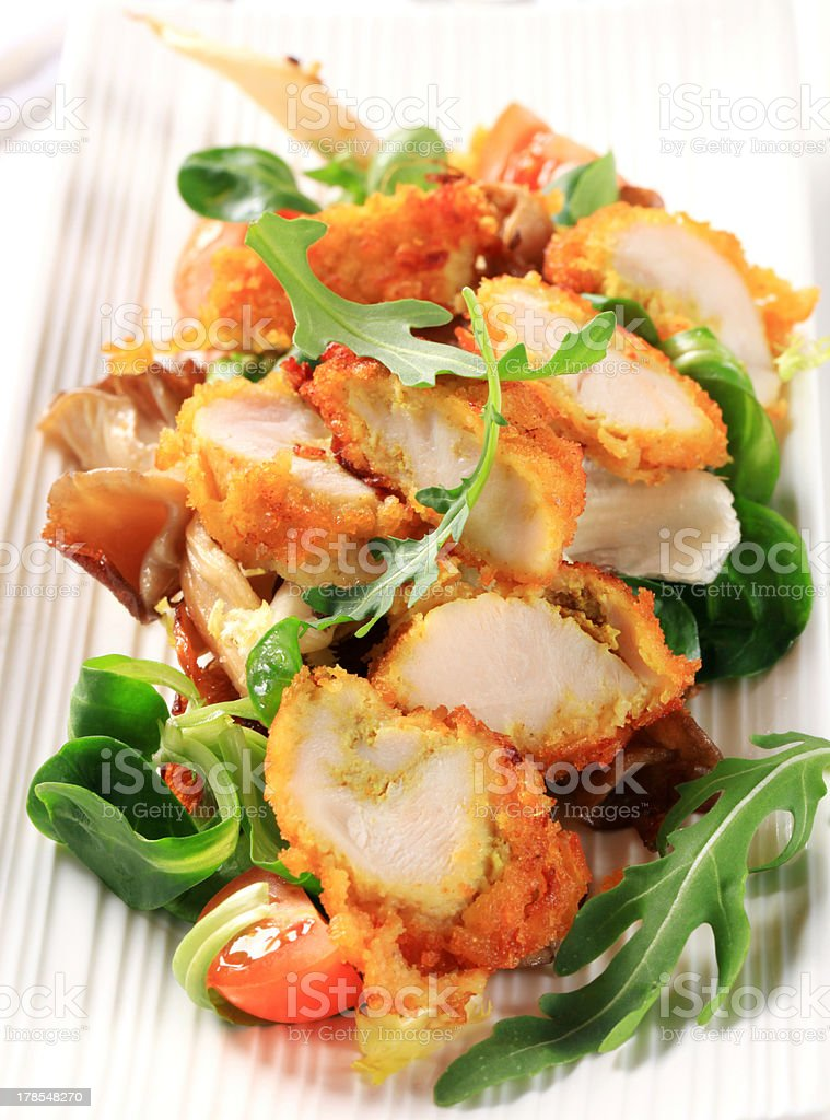 Breaded chicken breast with salad greens royalty-free stock photo