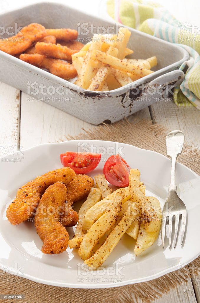 breaded chicken nuggets, french fries and tomato on a plate stock photo