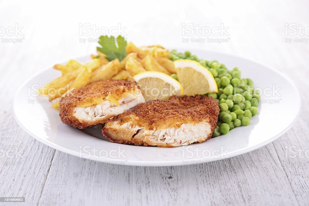 breaded meat and french fries stock photo