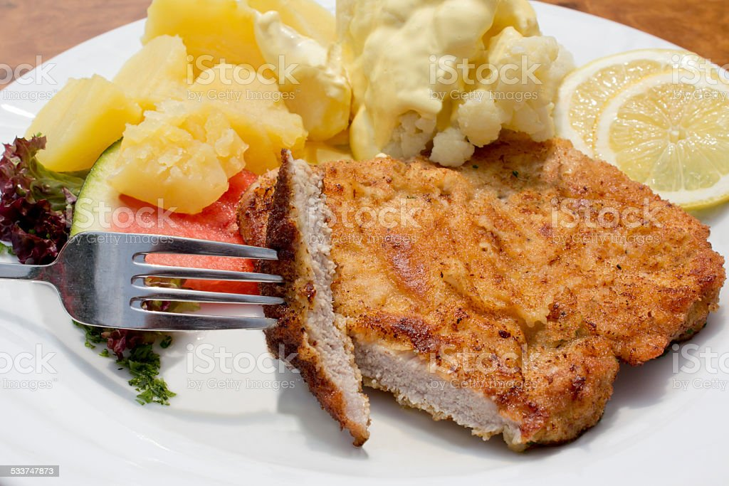 Breaded pork cutlet with boiled potatoes, cauliflower and hollandaise sauce stock photo
