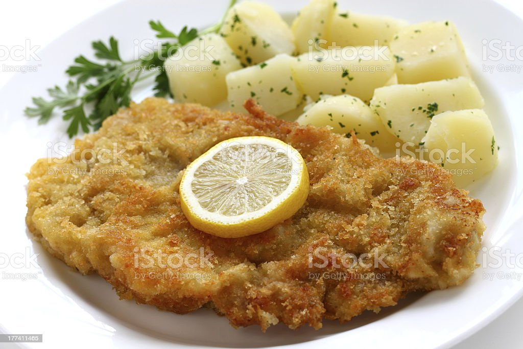 Breaded veal cutlet served with potatoes and lemon slice stock photo