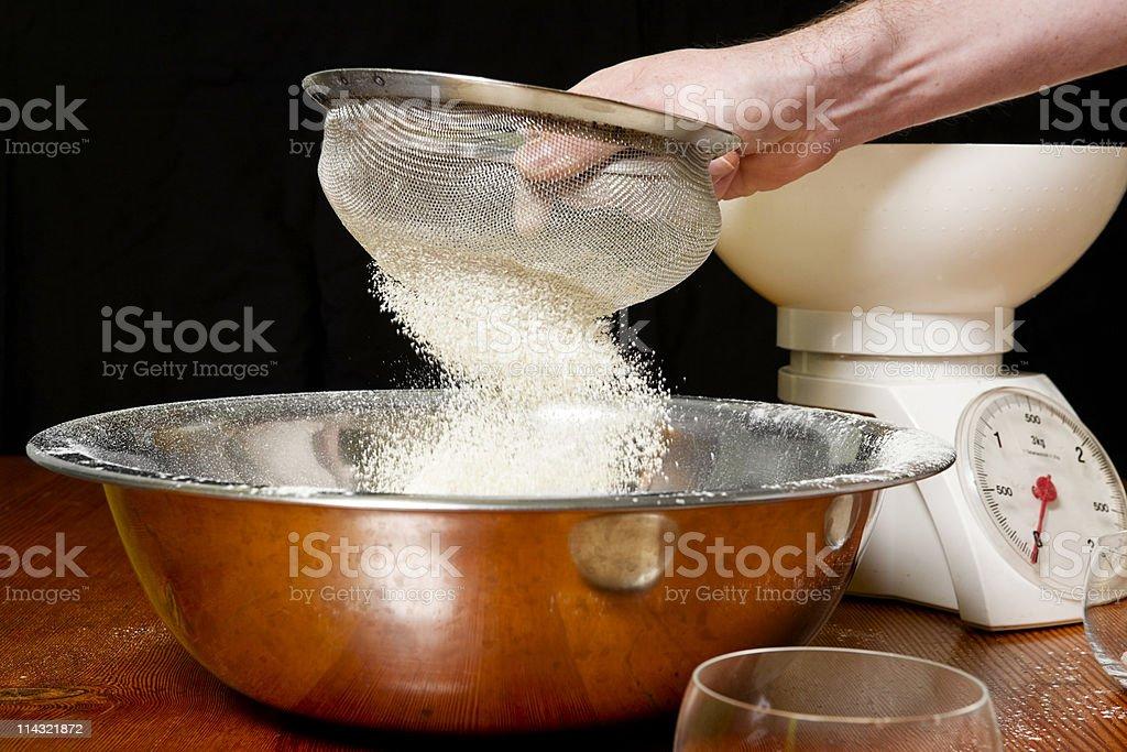 Breadmaking: Sifting flour royalty-free stock photo