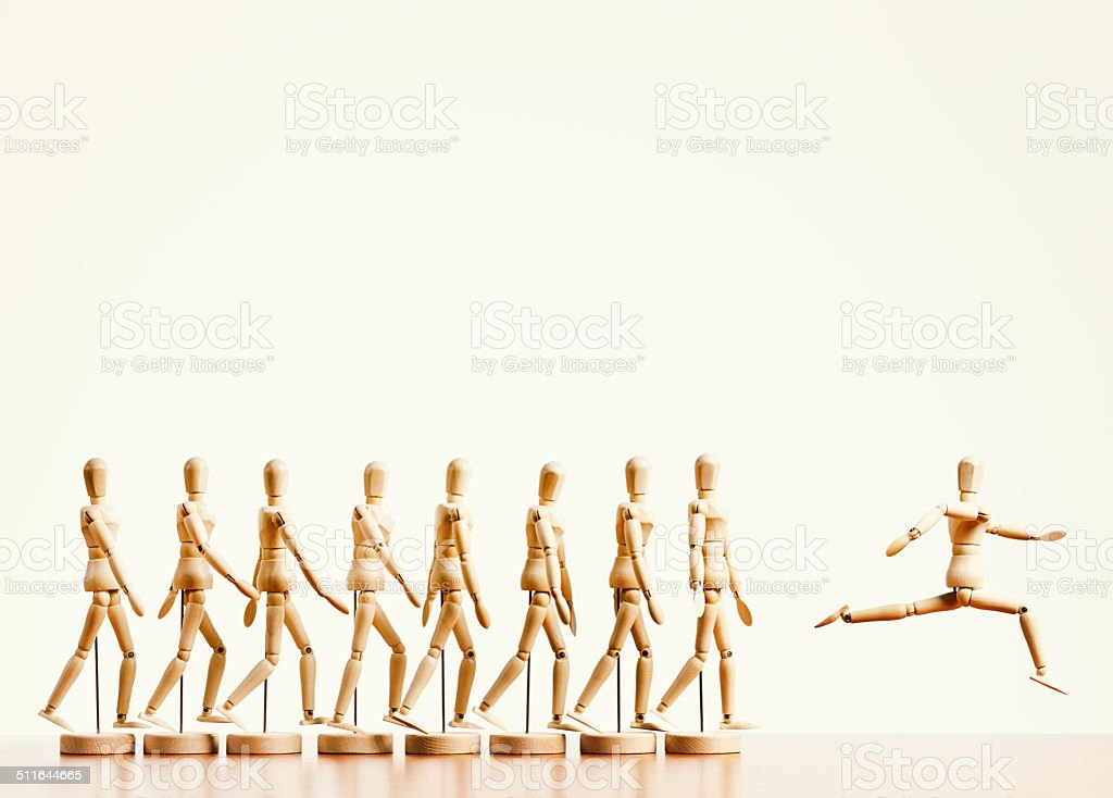 Breakaway! Single puppet leaps ahead of marching line. Non-conformist leader! stock photo