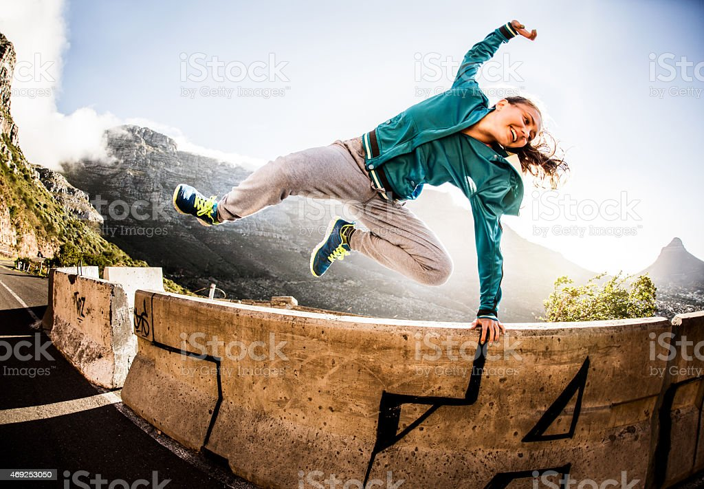 Breakdancer full of vitality jumping over a wall parkour style stock photo