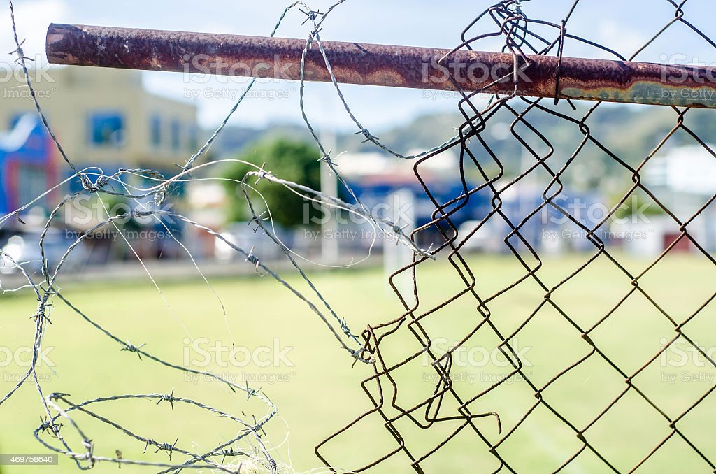 breakdown of security; rusty broken chain link fence close up stock photo