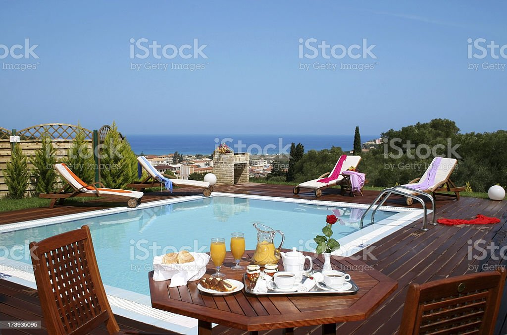 Breakfast al-fresco by the swimming pool at a vacation villa royalty-free stock photo