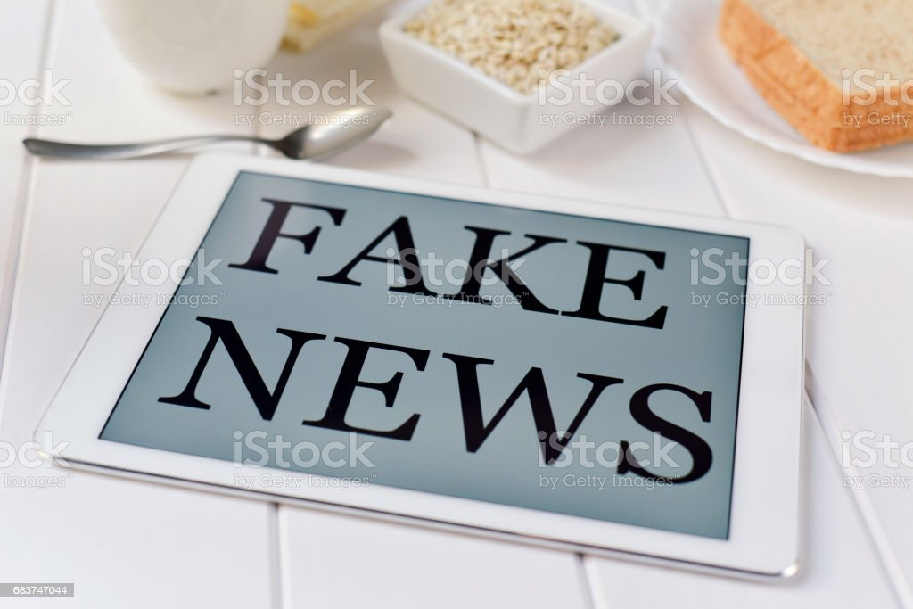 breakfast and text fake news in a tablet stock photo