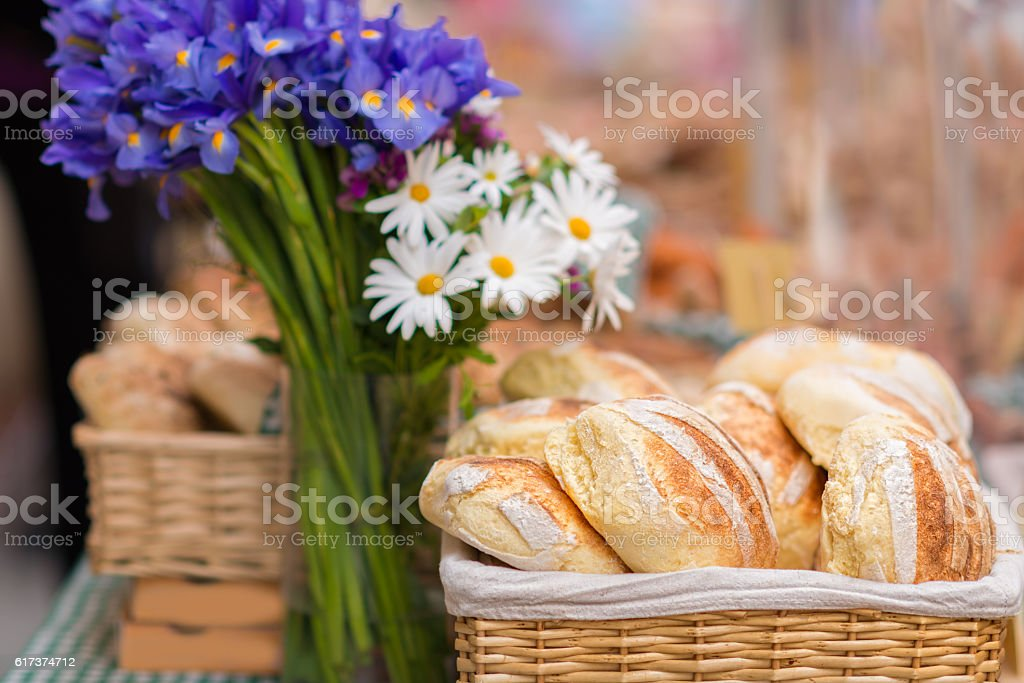breakfast baguettes in basket and flowers - german Brötchen stock photo