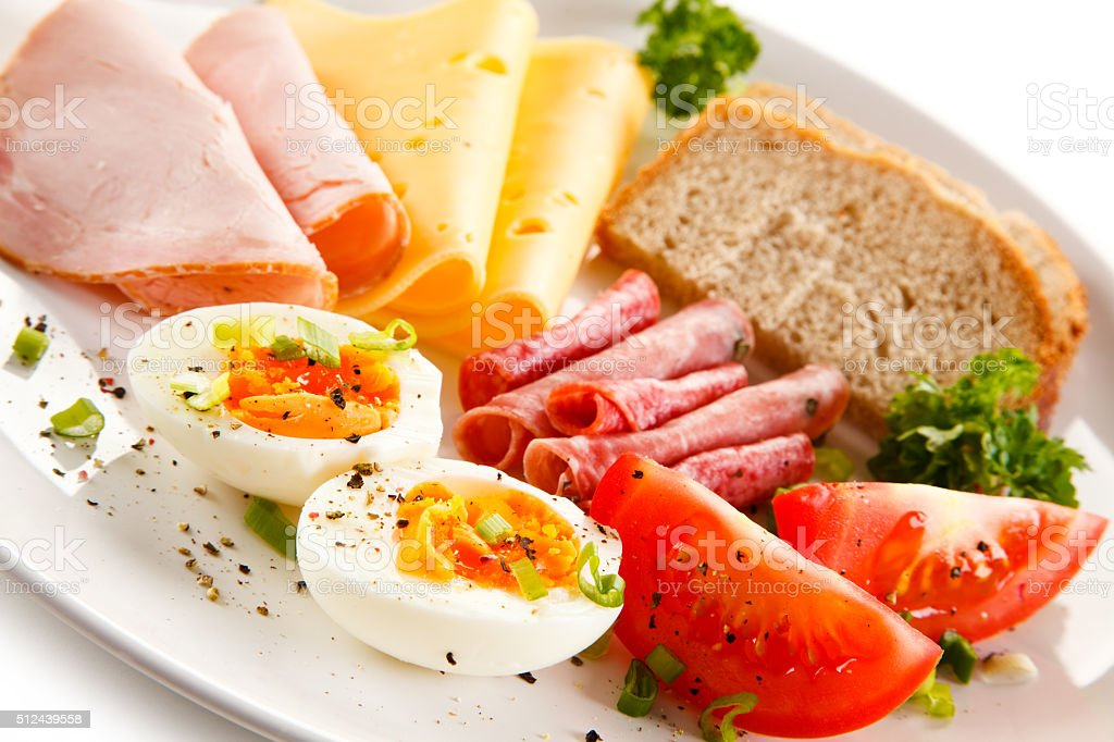 Breakfast - boiled eggs, bacon, ham and vegetables stock photo