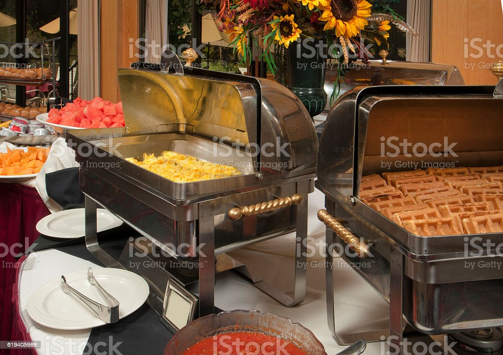 breakfast buffet line featuring eggs and waffles stock photo