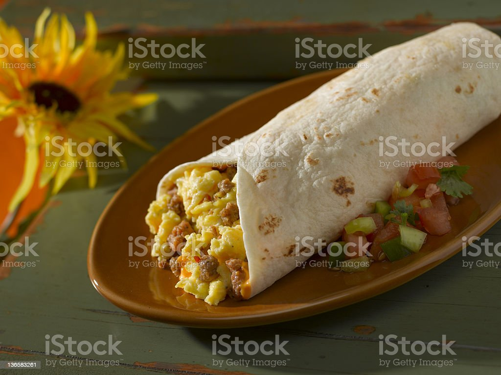 Breakfast burrito and salsa on ceramic plate with sunflower stock photo