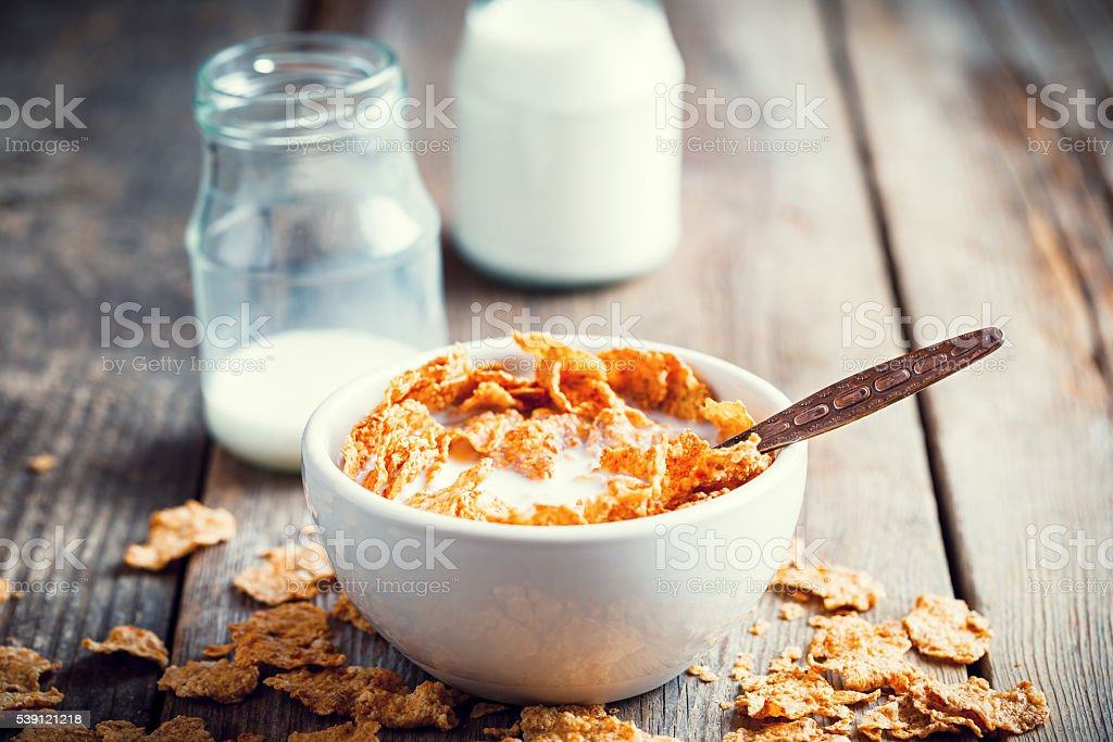 Breakfast cereal wheat flakes in bowl and milk bottles stock photo