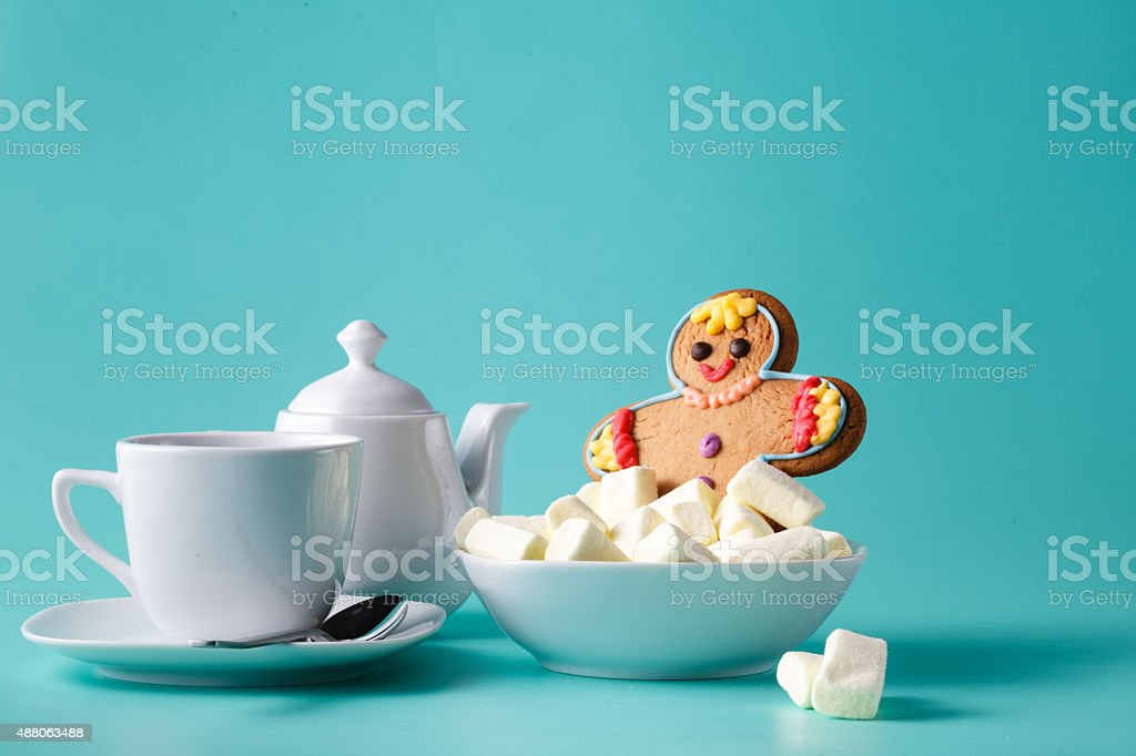 Breakfast concept. Gingerbread man swim in marshmallow stock photo