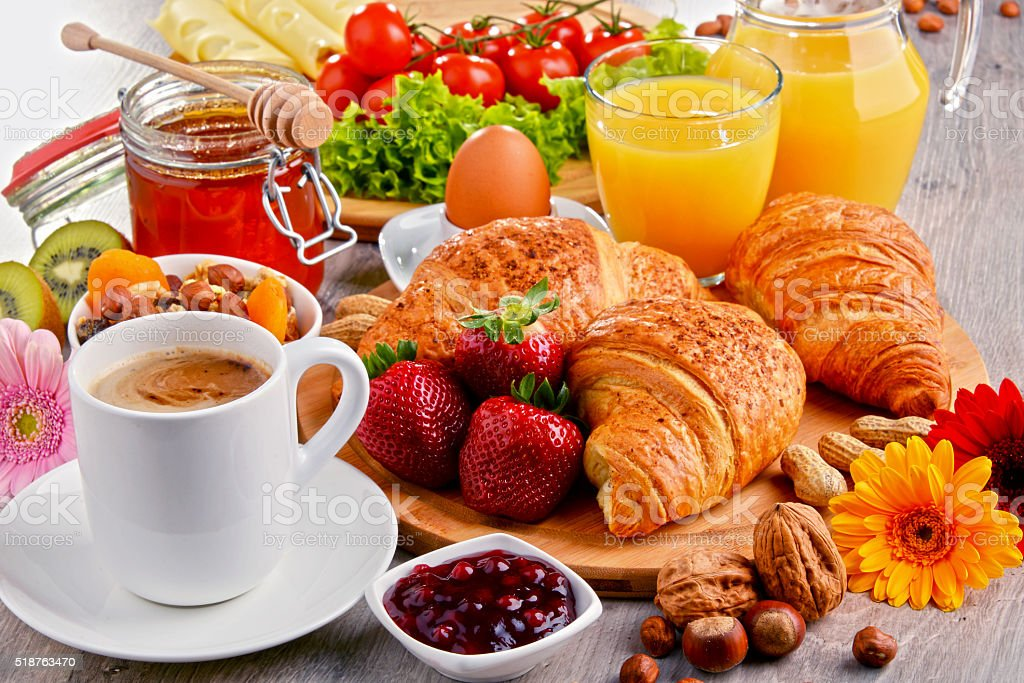 Breakfast consisting of croissants, coffee, fruits, orange juice stock photo