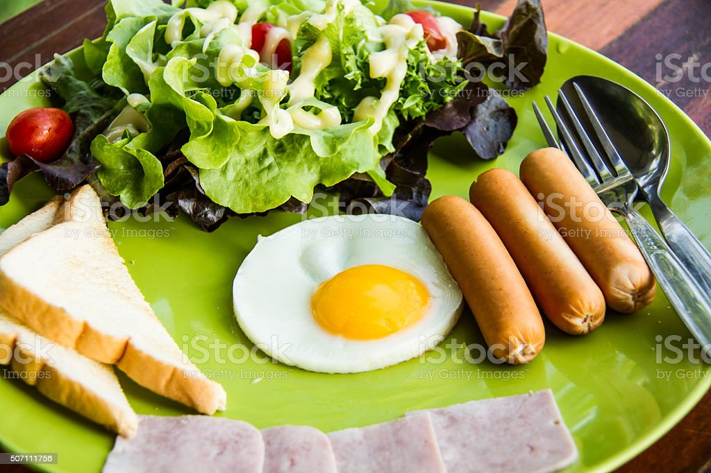 breakfast  consists eeg,salad,bread,bacon and sausage stock photo