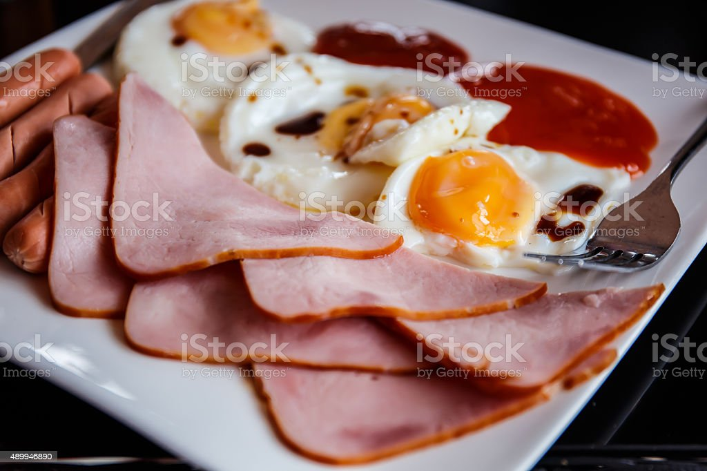 Breakfast consists of Fried egg, bacon, sausage stock photo