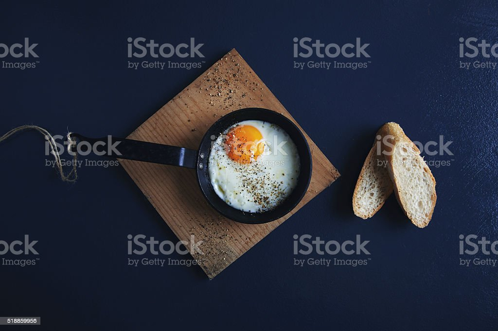 Breakfast fried eggs in vintage cast iron pan stock photo