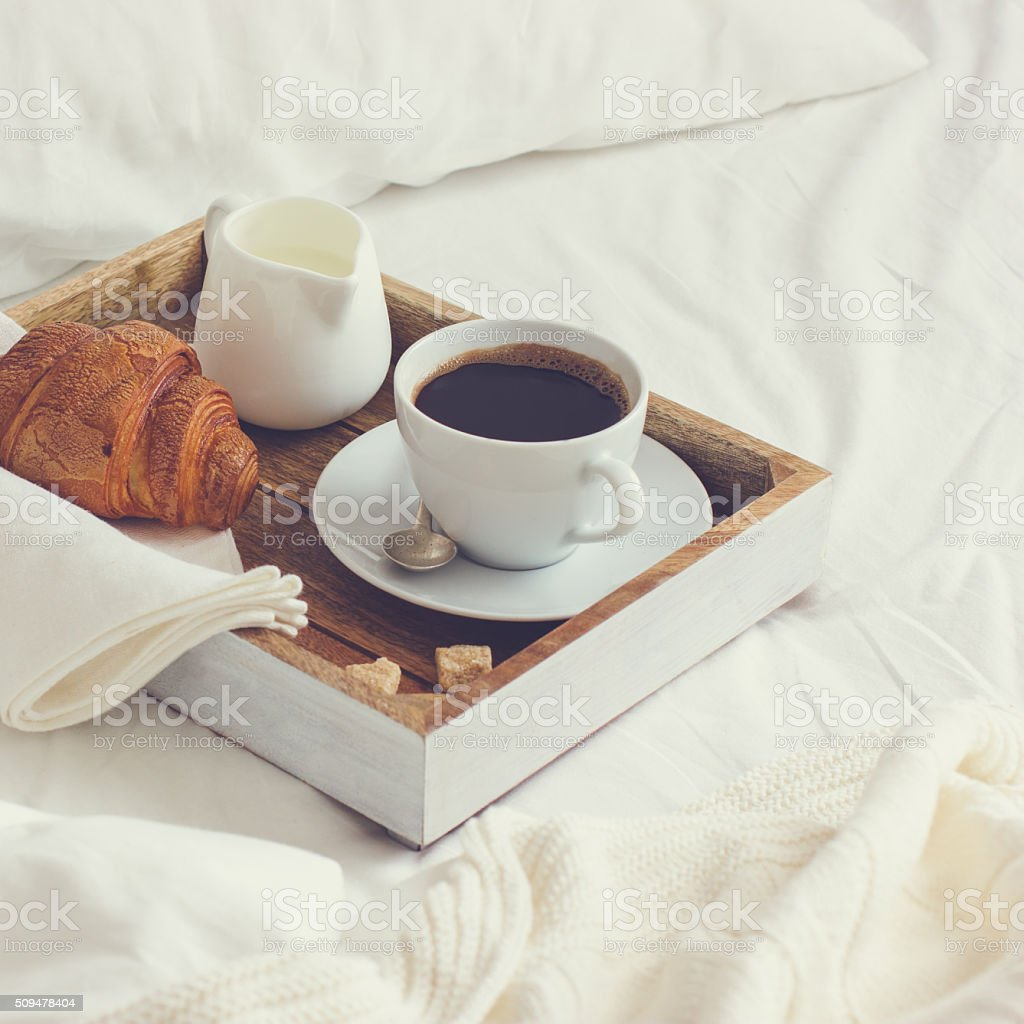 breakfast in bad,  tray with cup of coffee and  croissant stock photo