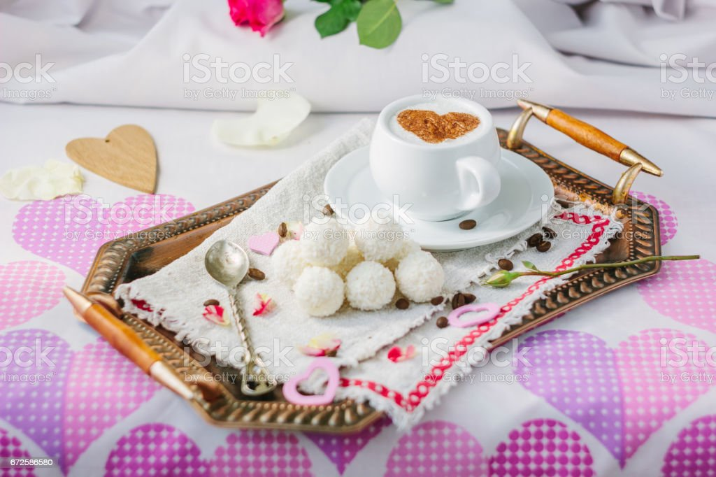 Breakfast in bed on copper tray over bed linens. stock photo