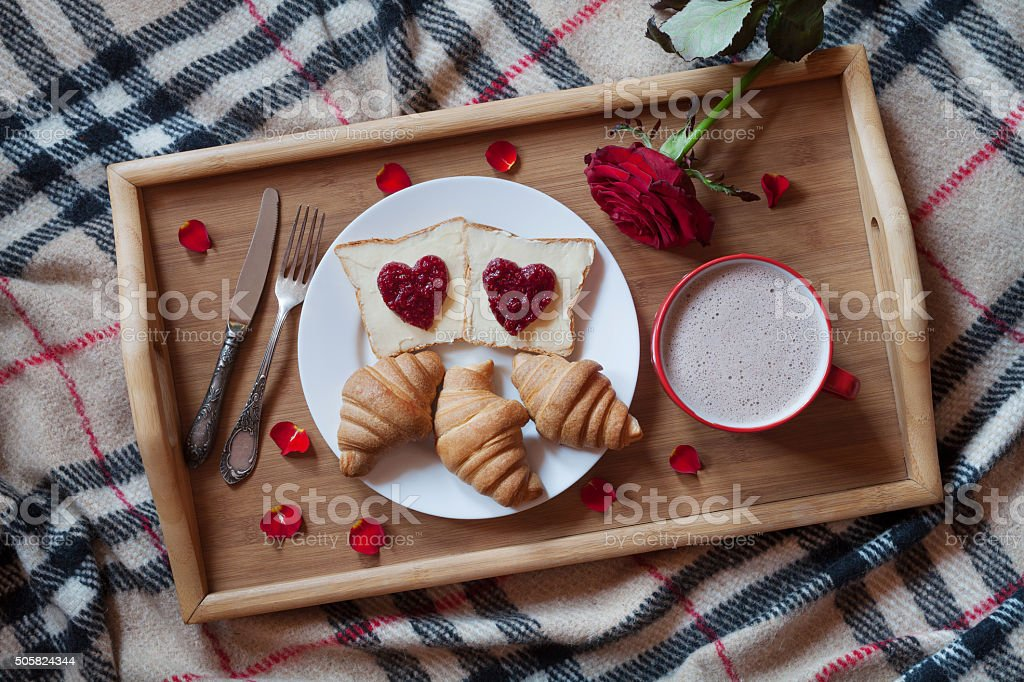 Breakfast in bed romantic surprise, toasts with jam, croissants and stock photo