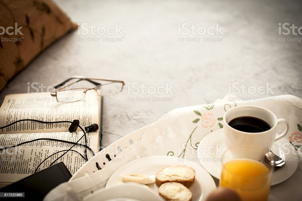 Breakfast in bed with book and mobile phone stock photo