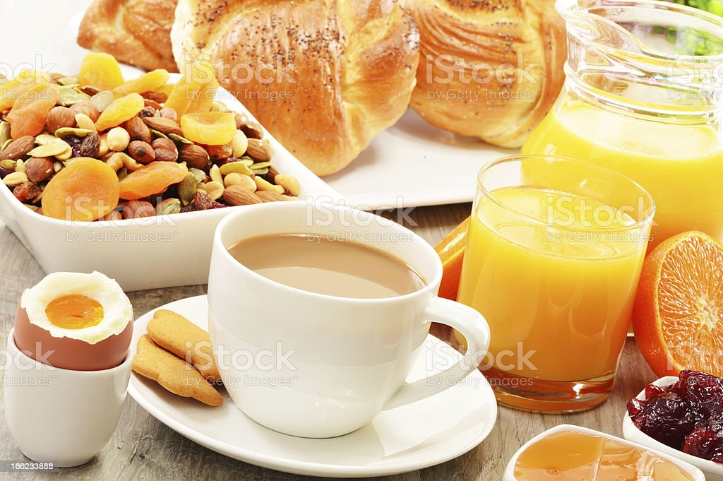 Breakfast including coffee, bread, honey, orange juice, muesli and fruits royalty-free stock photo
